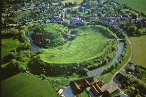 Aerial photo of Pleshey Castle. The castle consists of a grassy mound next to a kidney shaped enclosure, all surrounded by a moat. In the background is the village of Pleshey.