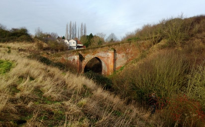 A brick bridge leading up to a motte and crossing a castle ditch