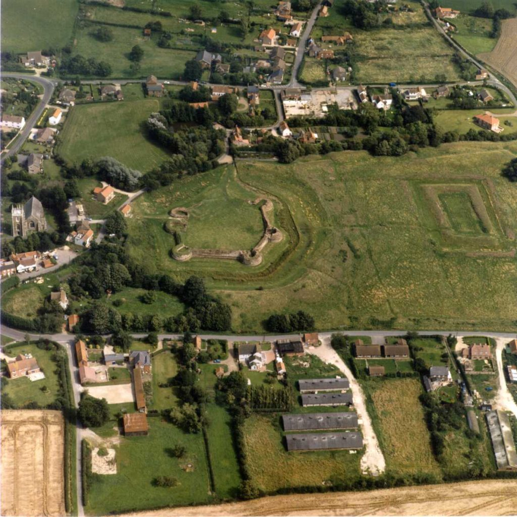 Aerial photo of a green field surrounded by houses. At one end of the field stand the remains of a hexagonal castle.